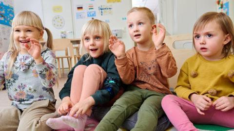 neljä lasta leikkii päiväkodin lattialla
