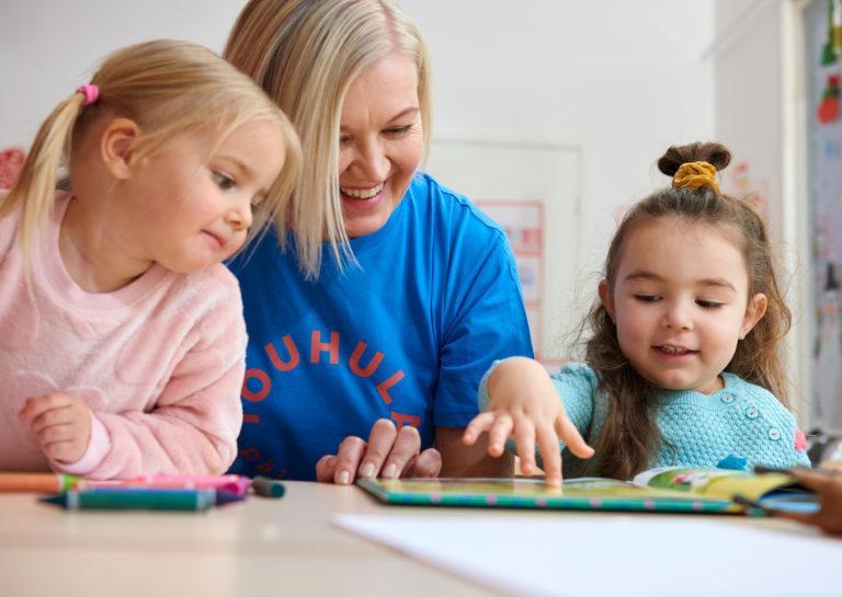 kaksi lasta ja lastenhoitaja tutkivat kuvakirjaa yhdessä