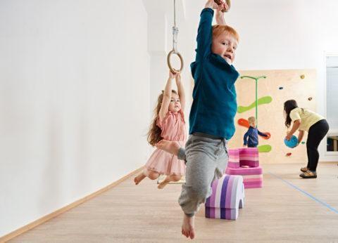 poika roikkuu jumppasalin voimistelurenkaissa