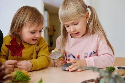 kaksi tyttöä tutkii kiveä suurennuslasilla päiväkodissa
