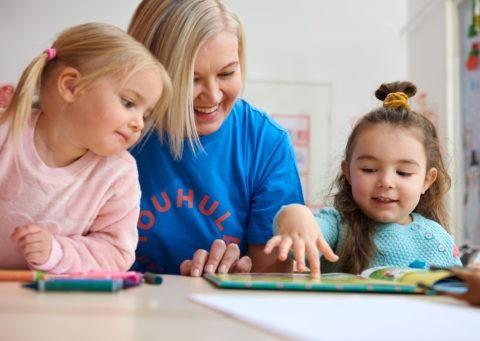 kaksi tyttöä ja lastenhoitaja tutkivat kuvakirjaa