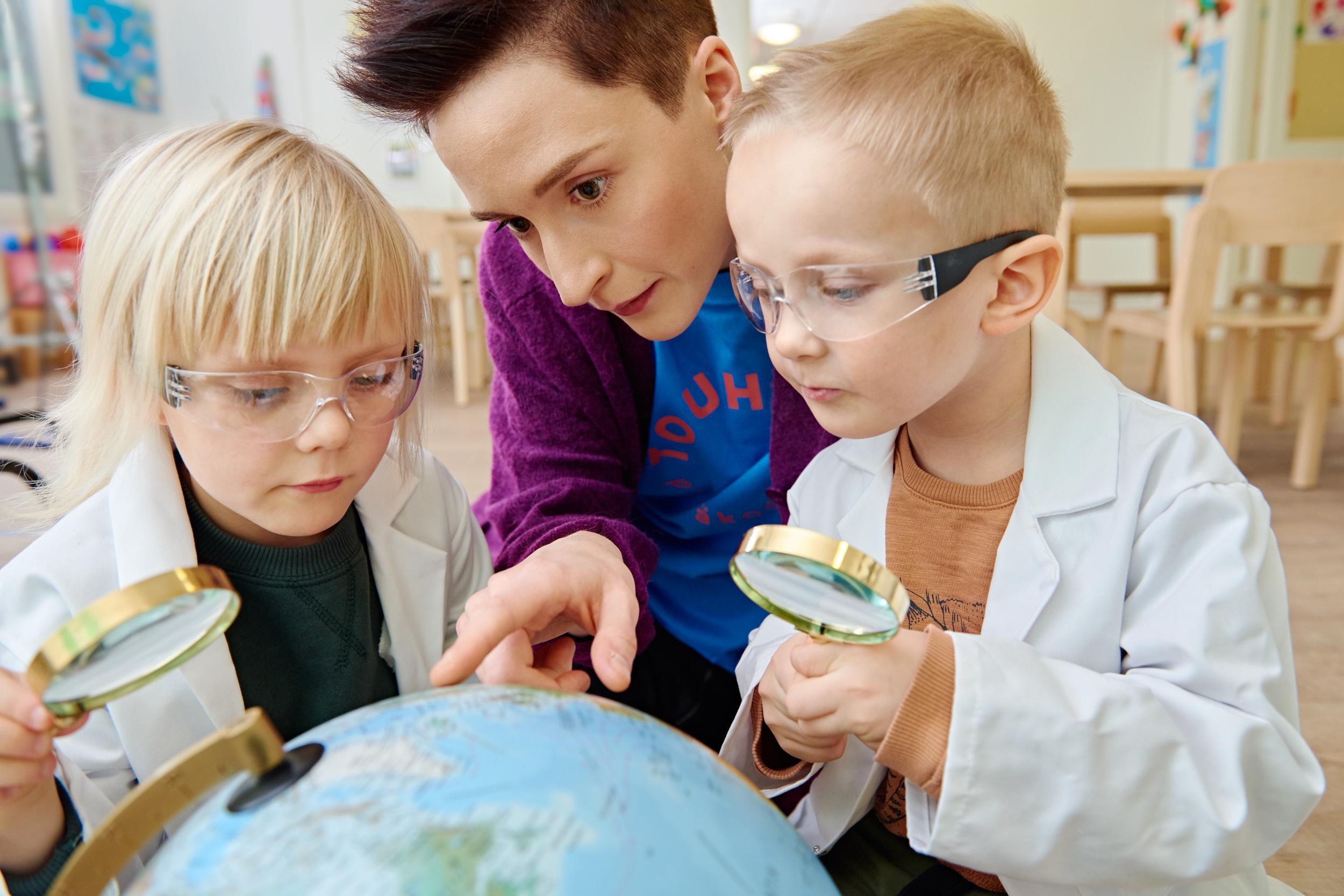 lapset ja lastenhoitaja tutkivat karttapalloa suurennuslaseilla