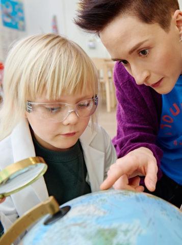 lapsi ja lastenhoitaja tutkivat karttapalloa