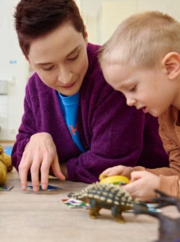 poika ja lastenhoitaja leikkivät dinosauruksilla