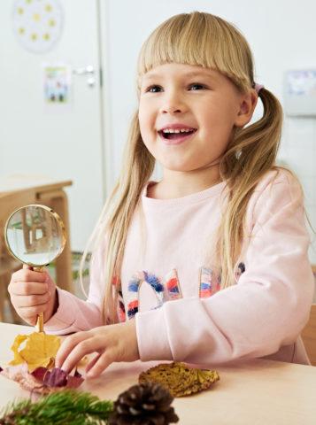 tyttö-havainnoi-ympäristöään-suurennuslasilla-tutkien